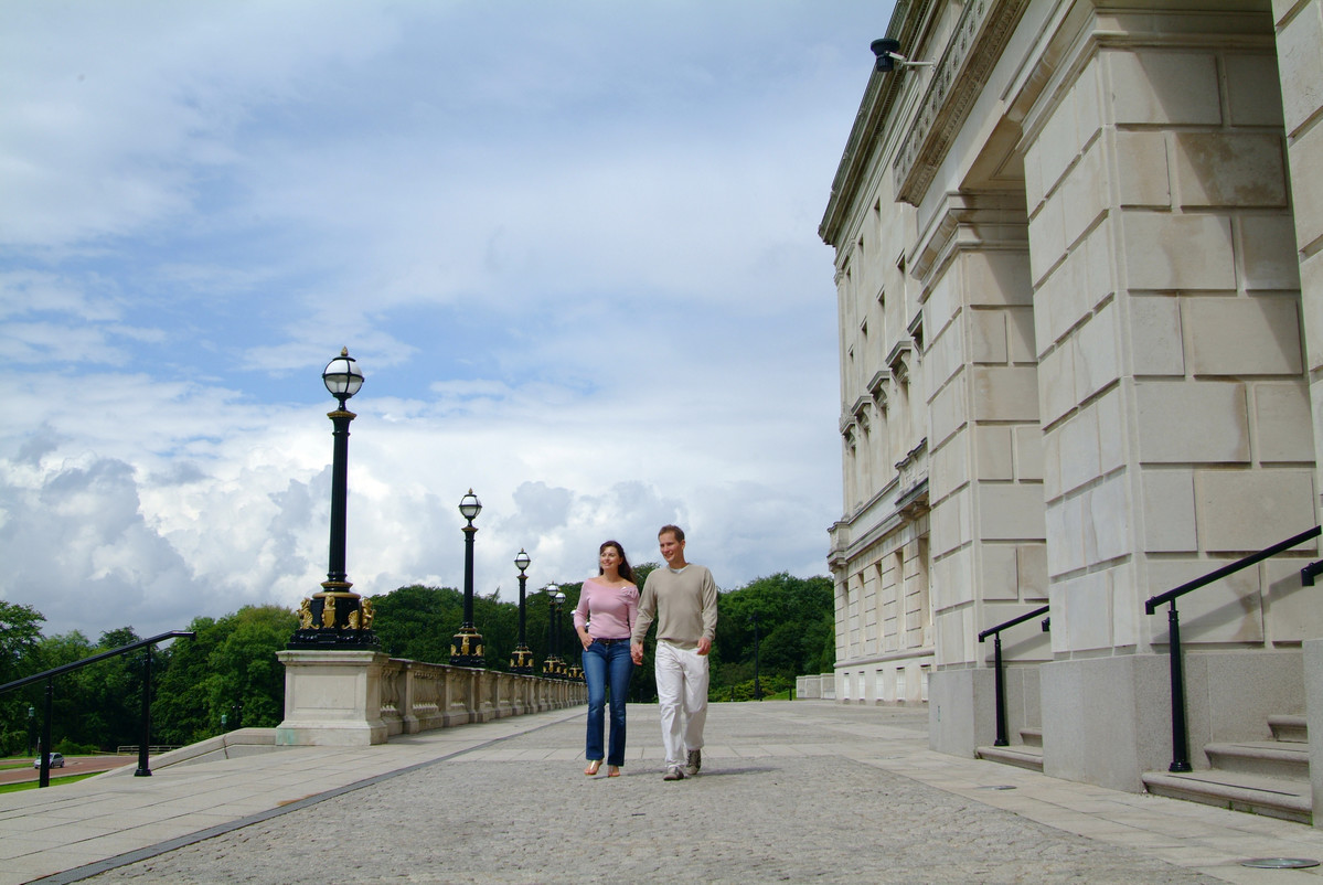 Man and woman walking in front of large white NI Parliament buildings