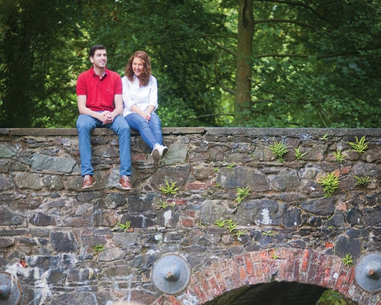 Man and woman sitting on stone wall