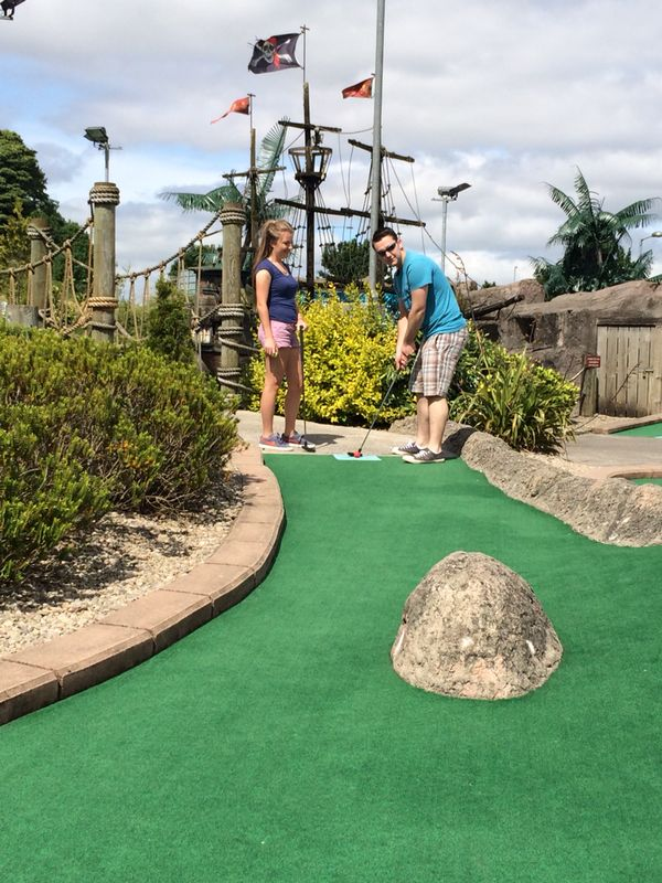 Man and woman playing mini golf