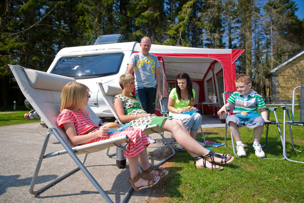 Family of five enjoying lunch outside their caravan