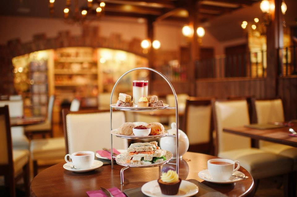 Table with afternoon tea stand filled with cakes, sandwiches, and other sweet treats